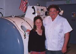 Dr. Donald Jolly Gabriel PhD and Denise Hetrick of Clear Mind Center standing in front of a Hyperbaric Oxygen device.